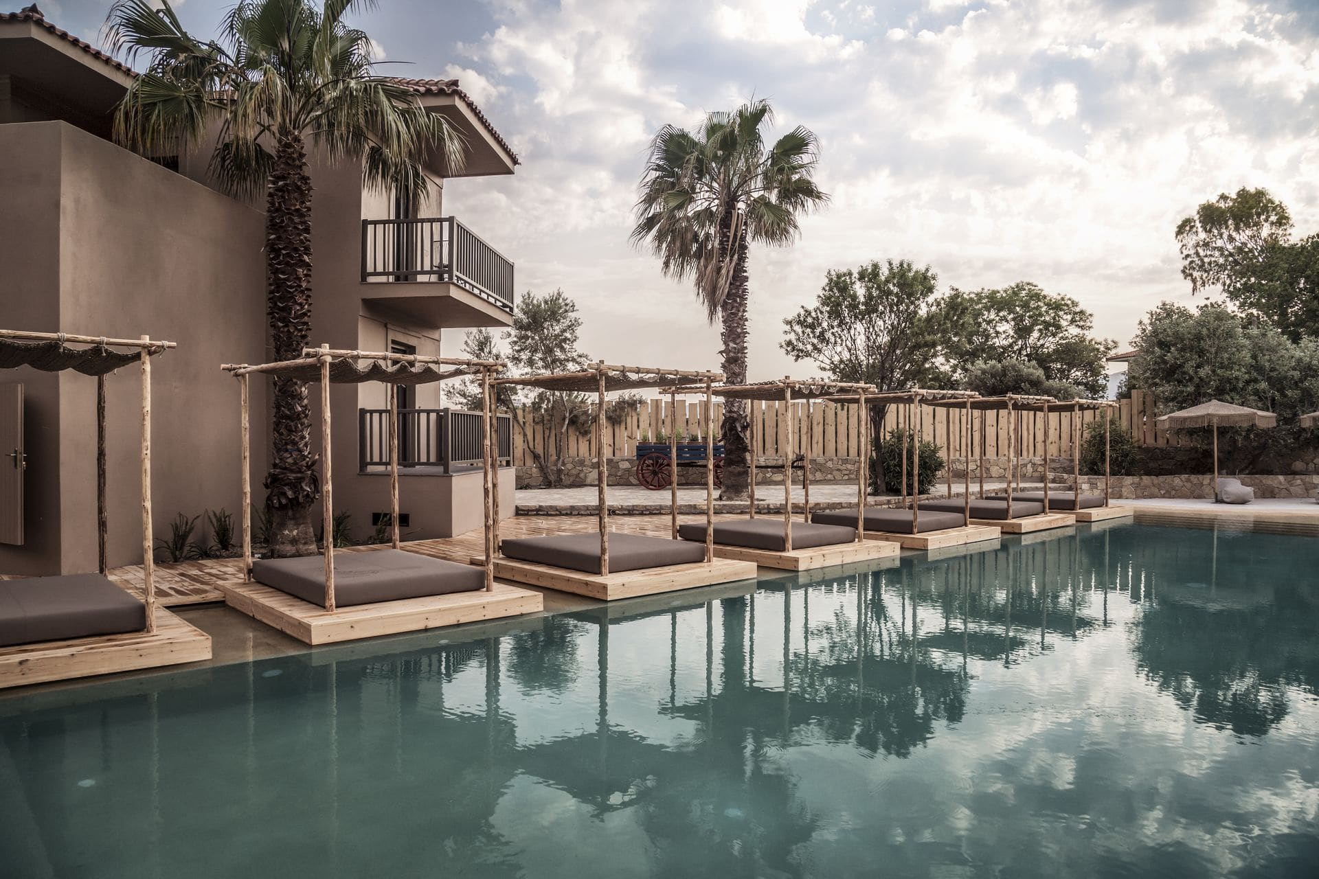 The pool and surrounding sun loungers and palm trees at Doryssa boutique hotel in samos