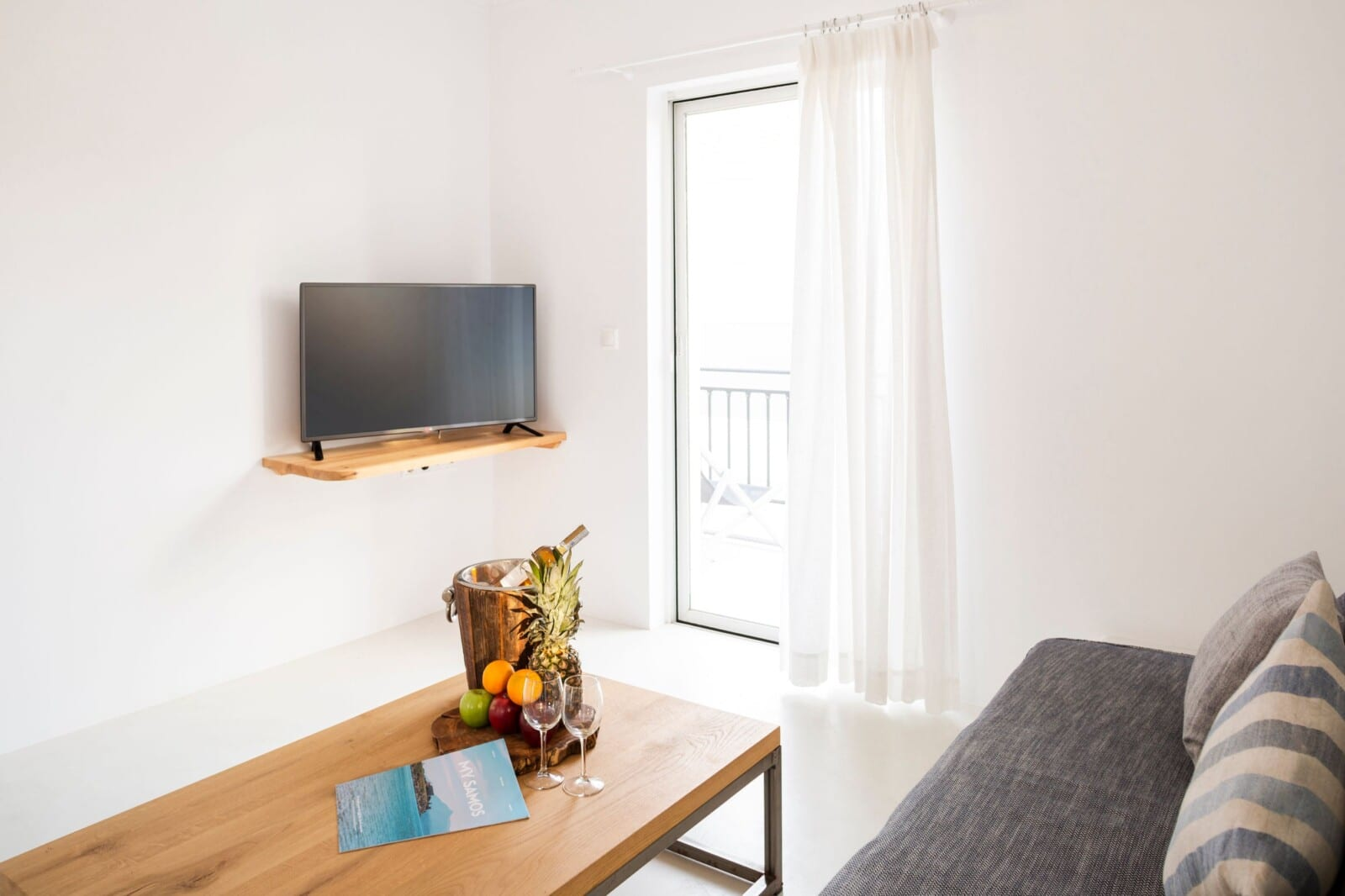 Living room table and TV at Doryssa Coast's family apartments in Samos